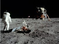 Aldrin stands next to the Passive Seismic Experiment Package with the Lunar Module in the background