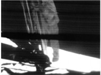 A mounted slowscan TV camera shows Neil Armstrong as he climbs down the ladder to surface.
