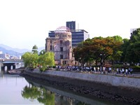 Citizens of Hiroshima walk by the Hiroshima Peace Memorial, the closest building to have survived th