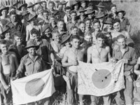 Australian soldiers display Japanese flags they captured at Kaiapit, New Guinea in 1943.