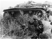 Infantry and a supporting StuG III assault gun advance towards the city center.
