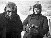 Red Army soldier marches a German soldier into captivity.