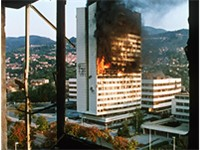 The parliament building in the centre of Sarajevo burns after being hit by tank fire during the sieg