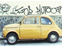 A mustard Fiat 500 in London, UK.
