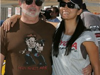 "Kelly Hu with George Lucas, Willow Springs Raceway, CA. The shirt worn by Lucas says, ""Han shot firs"