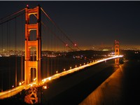 The Golden Gate Bridge by night, with part of downtown San Francisco visible in the background at fa
