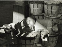Man sleeping in a Baltimore fish market in July 1938.