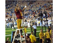 Sanchez, holding the sword of the USC drum major, salutes the fans after a victory in his final regu