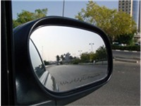 Arabic language objects warning on the passenger side door mirror.