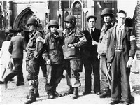 Dutch resistance members with troops of the US 101st Airborne in front of Eindhoven cathedral during