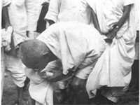 Gandhi at Dandi, April 5, 1930, picking up a lump of salty mud.