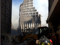 A New York City firefighter looks up at the remains of the South Tower.