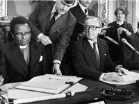 Bishop Abel Muzorewa signs the Lancaster House Agreement seated next to British Foreign Minister Lor
